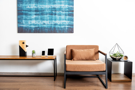 furniture: Table with comfy chair and bright picture in shiny apartment
