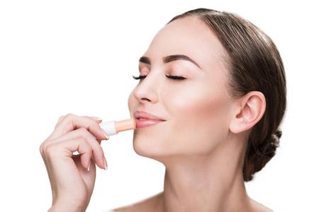 Happy beautiful girl applying make-up Banco de Imagens