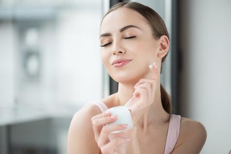 Alegre jovencita disfrutando mientras usa cosméticos faciales
