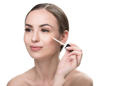 Happy beautiful girl applying visage cosmetic Stock Photo
