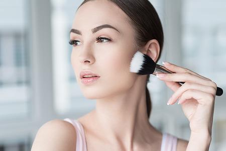 Ernstige aantrekkelijke vrouw die gezichtscosmetica toepassen