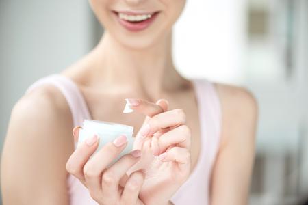 Youthful girl using day cream with joy Foto de archivo