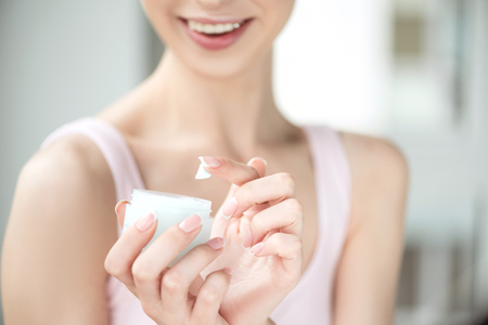 Youthful girl using day cream with joy Stok Fotoğraf