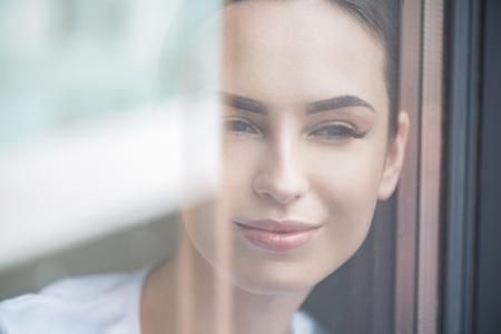 彼女のアパートから路上を見て幸せな若々しい女性