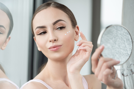 Happy youthful woman applying make-up on face skin