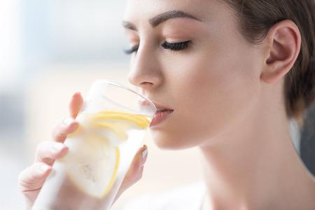 Ruhige junge Dame, die sich mit Zitronenwasser erfrischt