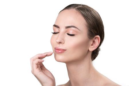 Joyful attractive girl feeling pleasure using facial cosmetics Banco de Imagens