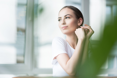 Joyful attractive girl resting after applying facial decorative cosmetic Stock Photo