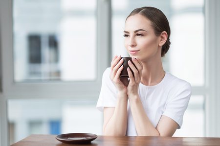 Thoughtful girl relaxing at home with mug of hot beverage