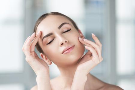 Happy beautiful girl adoring using facial cosmetics