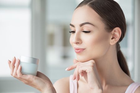 Happy beautiful woman enjoying using her make-up