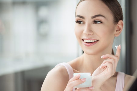 Beautiful happy girl using cosmetics for skin