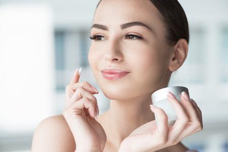 Gelukkige vrouw die gezichtscosmetica gebruikt Stockfoto