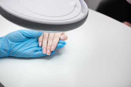 Cosmetologist is checking cuticles of young woman Stok Fotoğraf