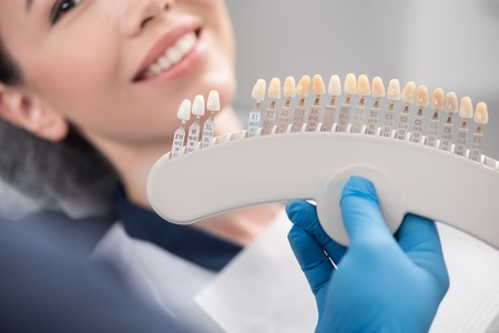 Odontologist arms showing teeth implants to patient Stock Photo