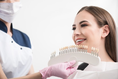 Odontologist selecting dental crown to outgoing woman