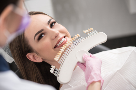 Physician enclosing dental crown to happy lady
