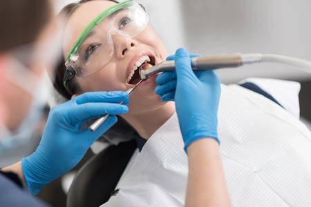 의사가 나가는 소녀의 치아를 고치기.