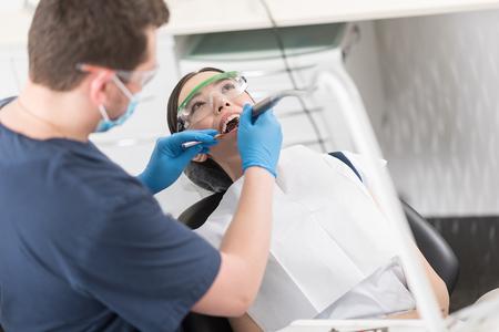 Dentist making treatment of happy lady