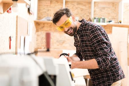 Joyful young woodworker is enjoying his work Stock Photo