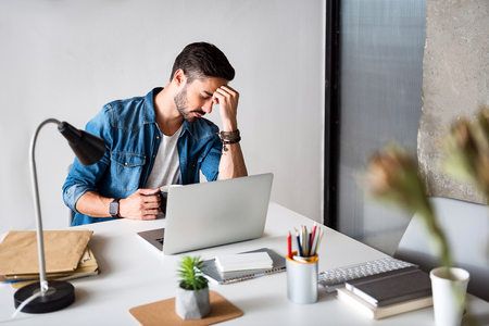 Tired worker hardly thinking about problem Stock Photo