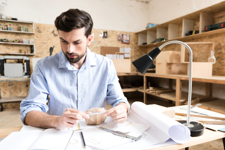 Concentrated youthful timber craftsman creating new sketches in workshop