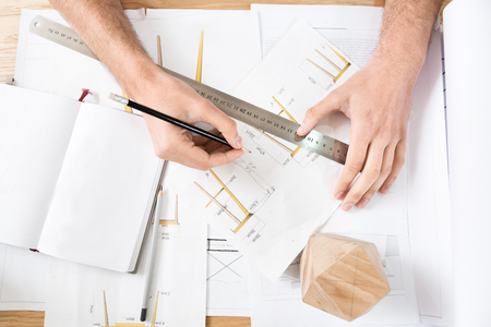 Timber craftsman drawing drafts at workplace