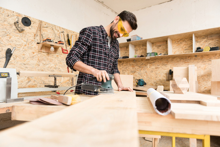 Positive young carpenter is laboring with pleasure