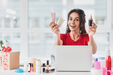 Opgewonden jonge vrouw celling cosmetica in internet