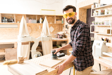 Attractive young carpenter is expressing happiness