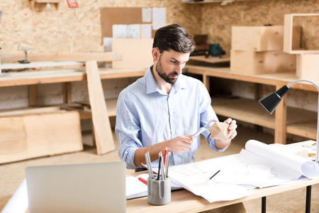 Concentrated bearded craftsman working on design of wooden object indoor