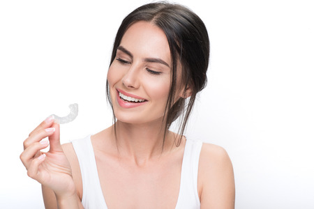 Joyful brunette girl ready for clear-aligner treatment Stock Photo