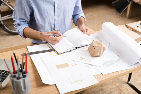 Lumber craftsman drawing drafts of manufacture at workplace