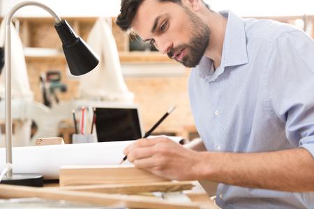 Grave barbudo carpintero haciendo dibujos en la pieza de madera en el lugar de trabajo Foto de archivo