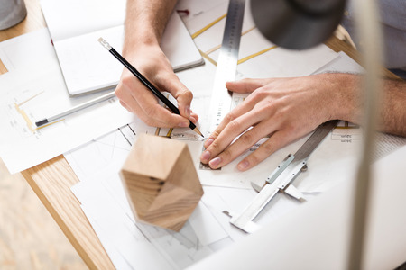 Lumber craftsman creating drafts of manufacture at workplace Stock Photo