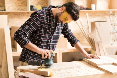 Attractive energetic carpenter is standing at his job Banque d'images