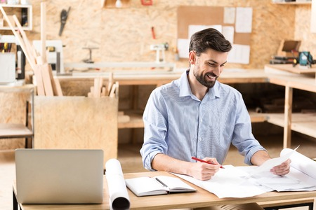 Happy youthful lumber craftsman creating sketches at his workplace Stock Photo