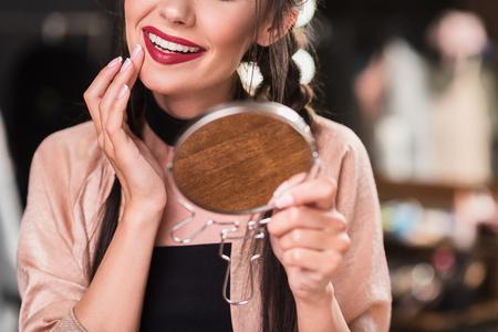 Beautiful young woman correcting makeup Stock Photo