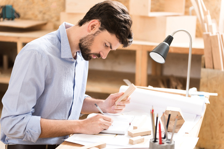 Concentrated youthful joinery master working on sketches at his desk Stock Photo