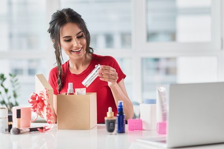 Cheerful girl making present with cosmetology Stockfoto
