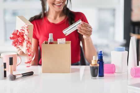 Carefree girl preparing cosmetic products as gifts