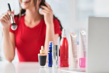 Blij meisje die samenstelling door professionele schoonheidsmiddelen doen