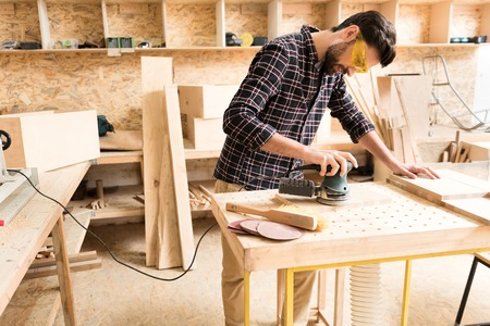 Cheerful woodworker is leaning on table while laboring with instrument Reklamní fotografie - 81368062