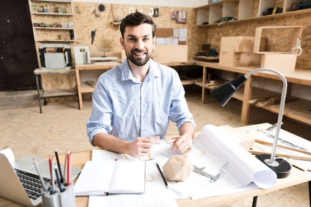 Joyful young timber craftsman drawing drafts of manufacture in workshop Фото со стока