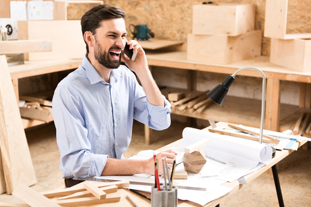 Pleasant cheerful carpenter is enjoying conversation by smartphone