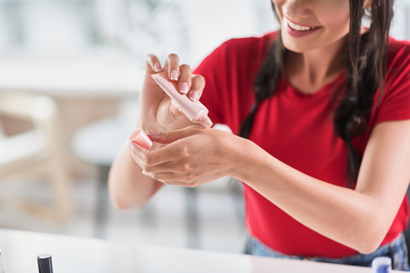 Confident girl preparing make-up base for her face