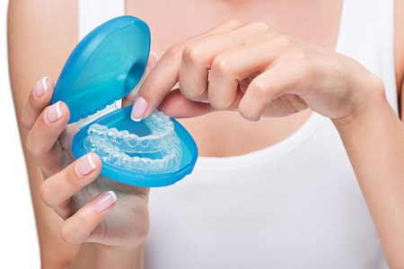Young woman holding cover with clear aligners