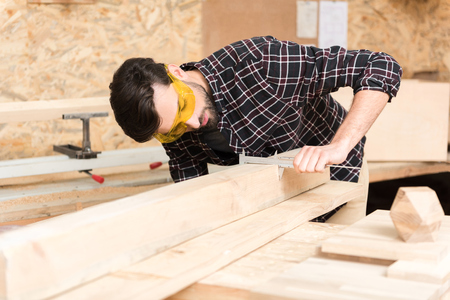 Experienced carpenter is laboring in workshop