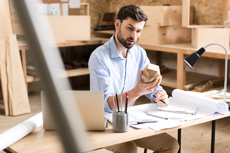 Thoughtful youthful lumber expert thinking over product sketches in workshop Stock Photo