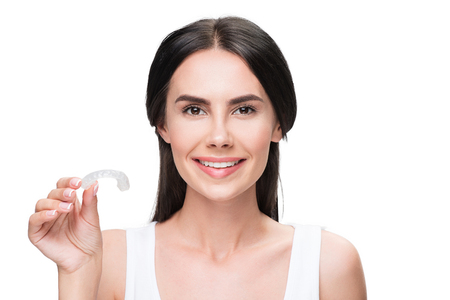 Cheerful young woman presenting clear-aligner treatment